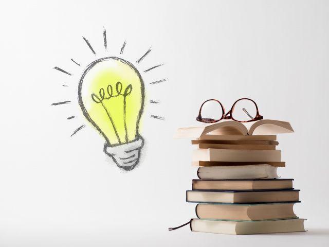 山積みにされた本と眼鏡と電球